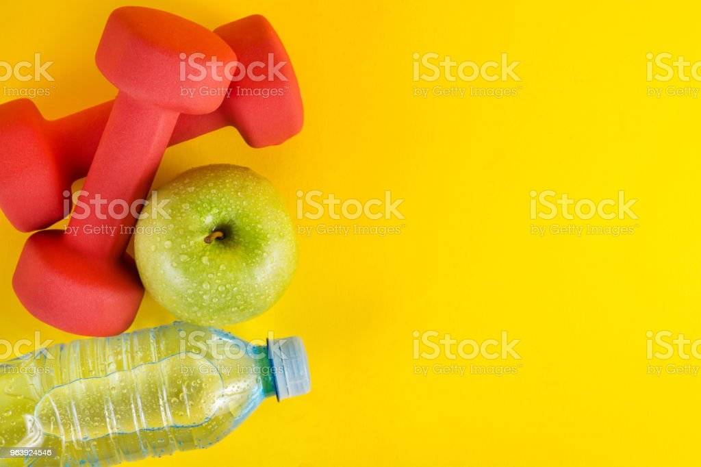 Top view of red dumbbells, green apple and fresh water bottle with dew on yellow background and space - Royalty-free Apple - Fruit Stock Photo