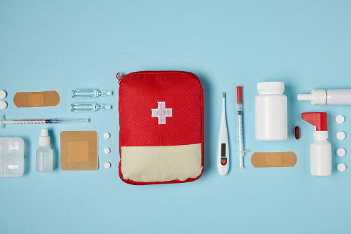 top view of red first aid kit bag on blue surface with medical supplies