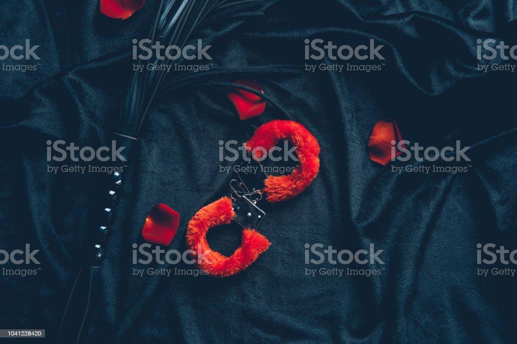 vista superior de rojo mullidas esposas, fustas de cuero y pétalos de rosa en tela negra foto de stock libre de derechos