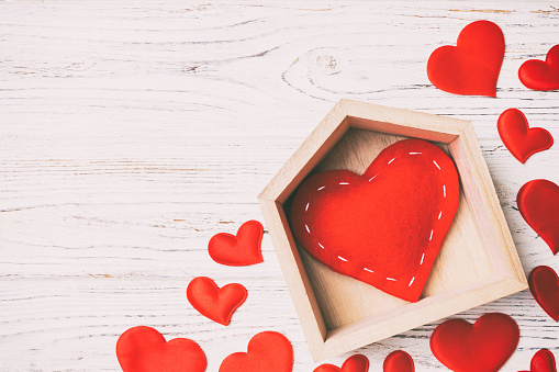 Top view of red heart in a house decorated with small hearts on wooden background. Valentine's day. Home sweet home concept.