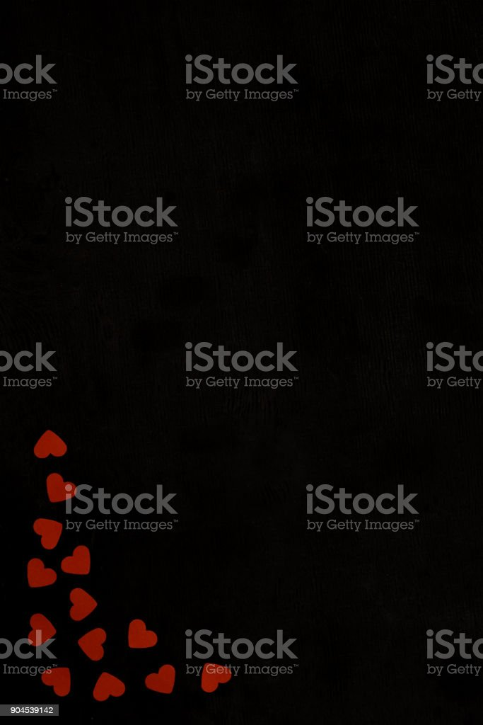 top view of red heart shaped confetti isolated on black stock photo
