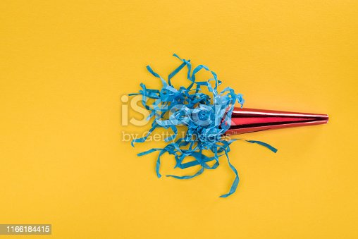 Top view of red party horn with blue paper confetti on yellow background