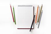Design concept - Top view of red spiral notebook and many color pencil collection isolated on white background for mockup