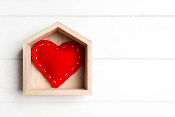 Top view of red textile heart in a house on wooden background. Home sweet home concept. Valentine's day stock photo