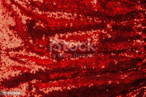 top view of red textile with shiny sequins as background