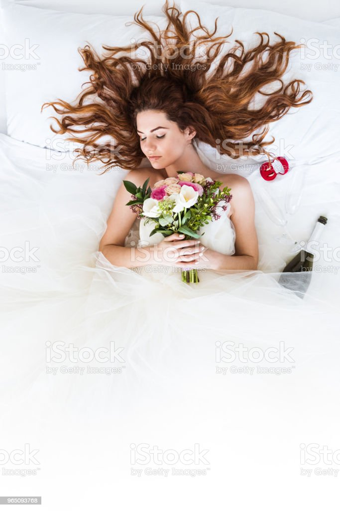 Top view of redhead bride wearing white dress sleeping in bed with flowers and wedding rings royalty-free stock photo