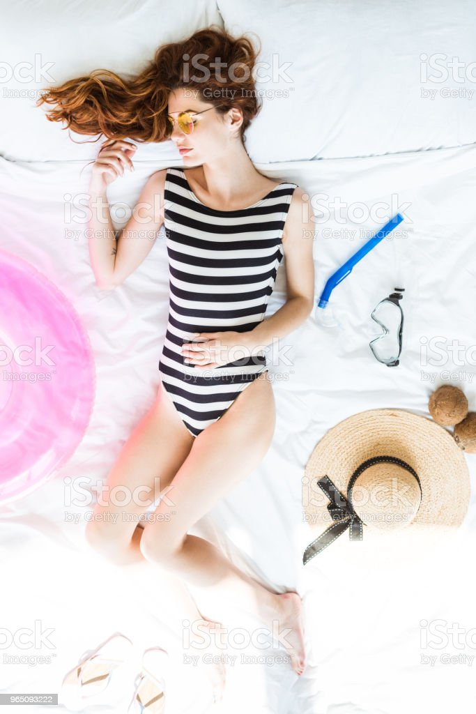 Top view of redhead girl in swimsuit sleeping on bed among travel objects royalty-free stock photo