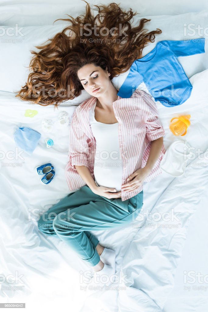 Top view of redhead pregnant woman sleeping in bed among baby clothes royalty-free stock photo