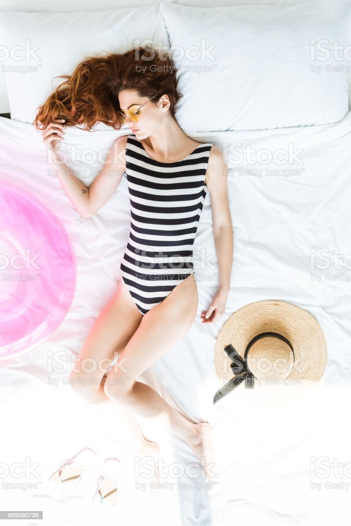 Top view of redhead woman in swimsuit sleeping on bed among beach objects royalty-free stock photo