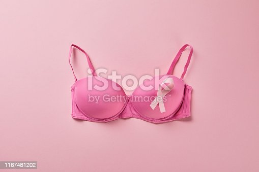 top view of ribbon on brassiere on pink background, breast cancer concept
