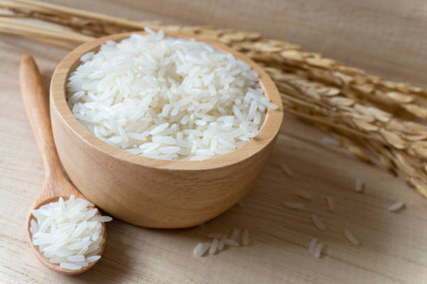 Top view of rice in a bowl and spoon on wood background. Top view of rice in a bowl and spoon on wood background. basmati rice stock pictures, royalty-free photos & images