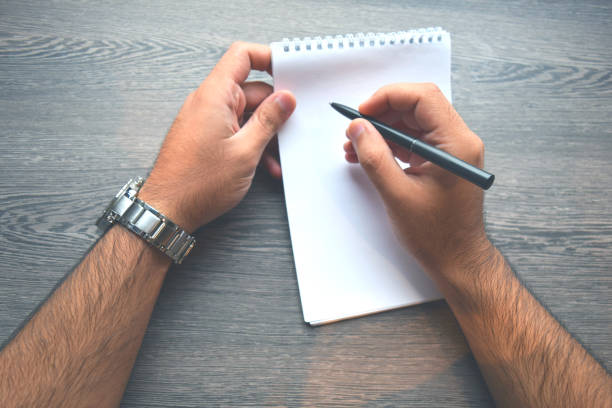 Top view of right handed man with metal silver watches and writing in notebook by black pen stock photo