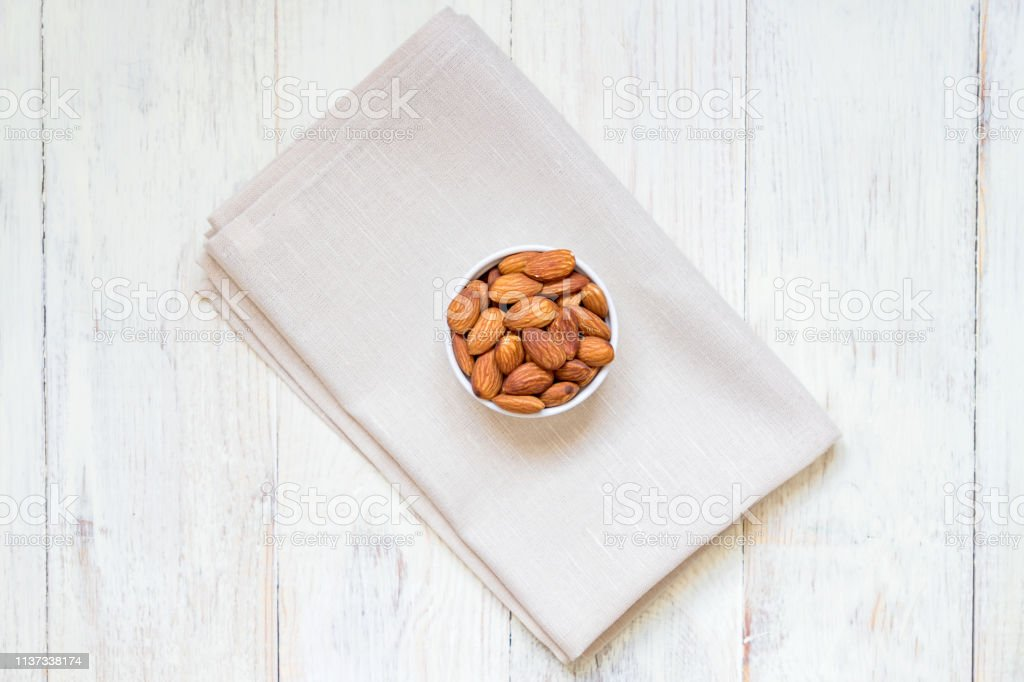 top view of Roasted Almonds in white porcelain bowl on textile napkin...