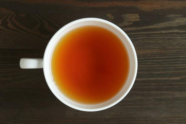 top blick auf geröstete barley tea oder japanisch mugicha auf dark brown wooden table - grüner tee koffein stock-fotos und bilder