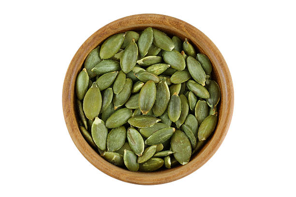 Top view of roasted pumpkin seeds in wooden bowl stock photo