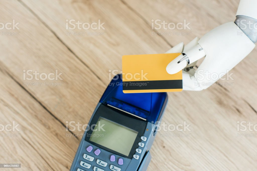 top view of robot holding credit card above payment terminal on wooden table royalty-free stock photo