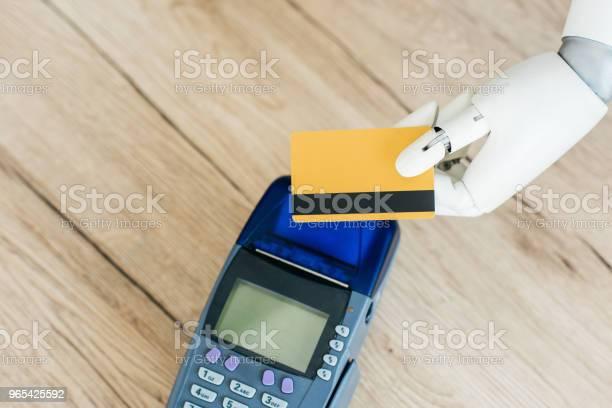Foto de Vista Superior Do Robô Segurando O Cartão De Crédito Acima Pagamento Terminal Na Mesa De Madeira e mais fotos de stock de Braço robótico