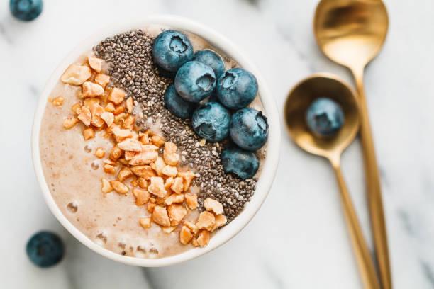 白い背景に、新鮮な熟したブルーベリー、ナッツ、チア、バナナ、大豆ミルク sa moothie ボウルの平面図です。健康的な食事、ベジタリアン料理のコンセプトです。 - 深皿 ストックフォトと画像