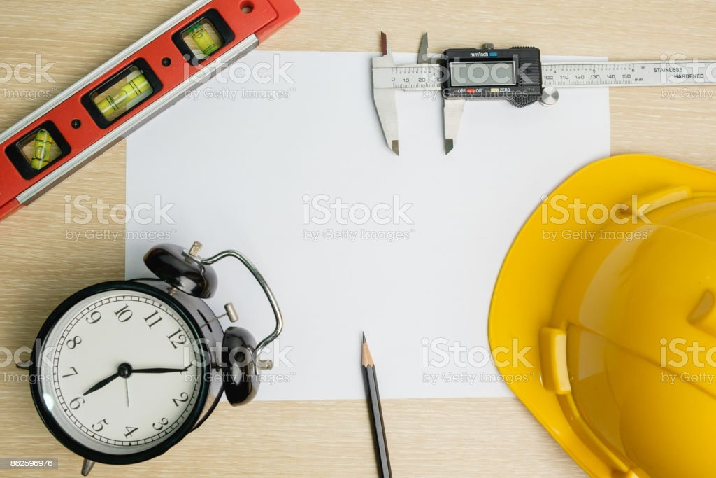 Top view of safety helmet, safety eye glasses, gloves, ear cushion and pencil on blank paper background. stock photo