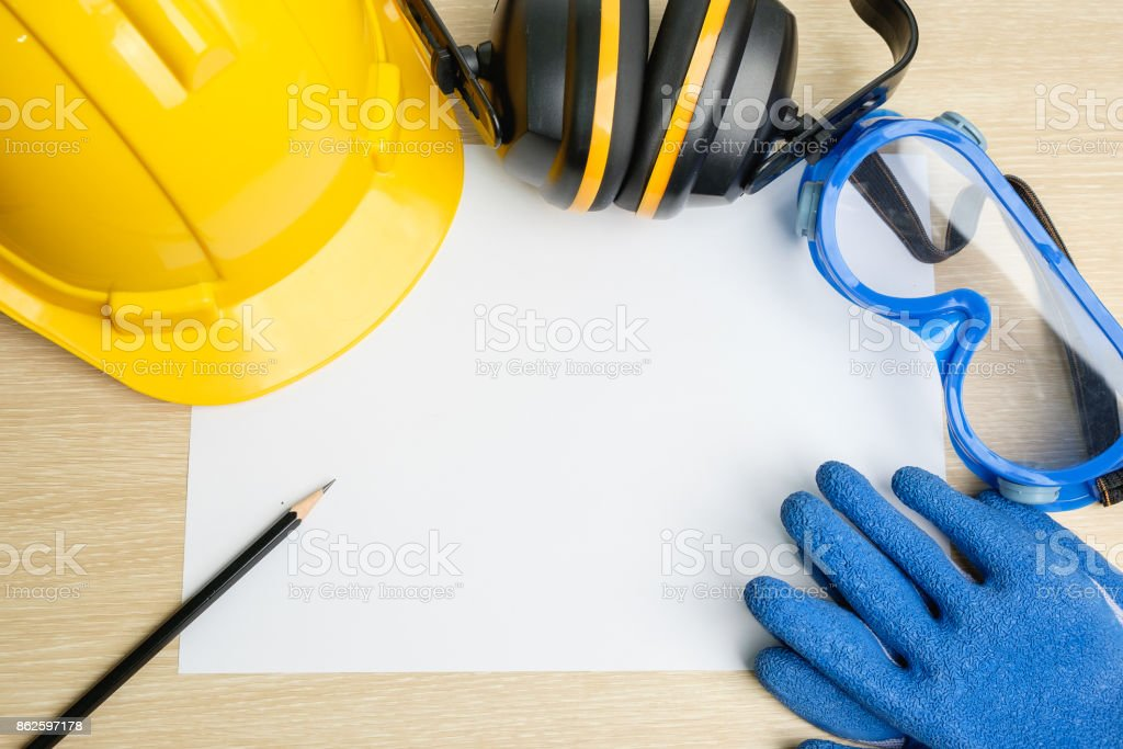 Top view of safety helmet, safety eye glasses,gloves, ear cushion and pencil on blank  paper background. stock photo
