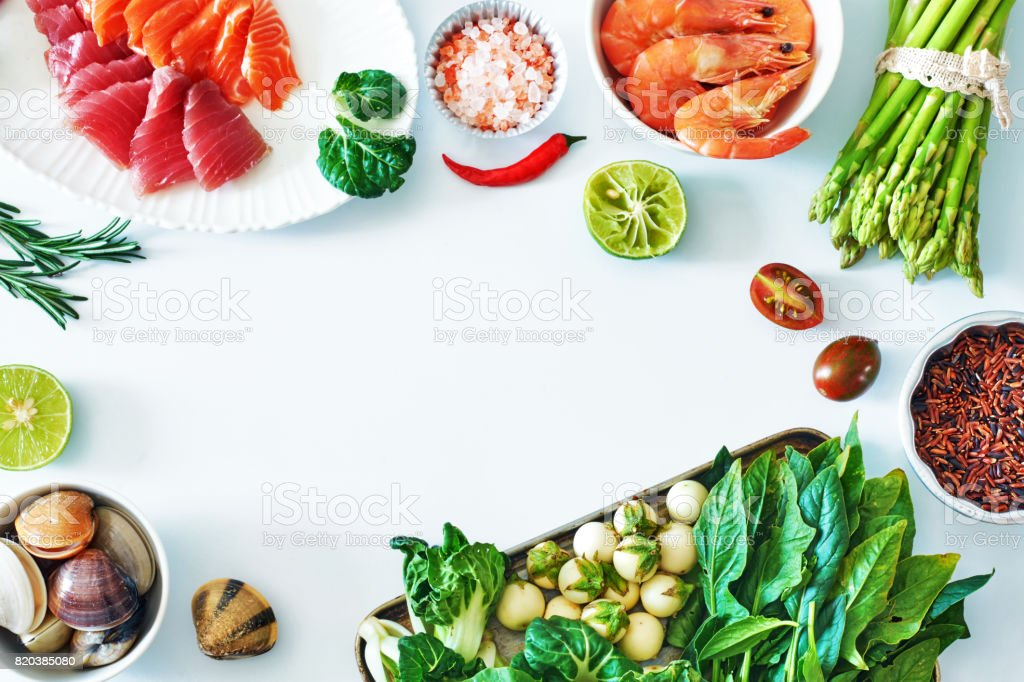 top view of salmon and tuna sashimi cooked shrimps clamps brown rice a green food background