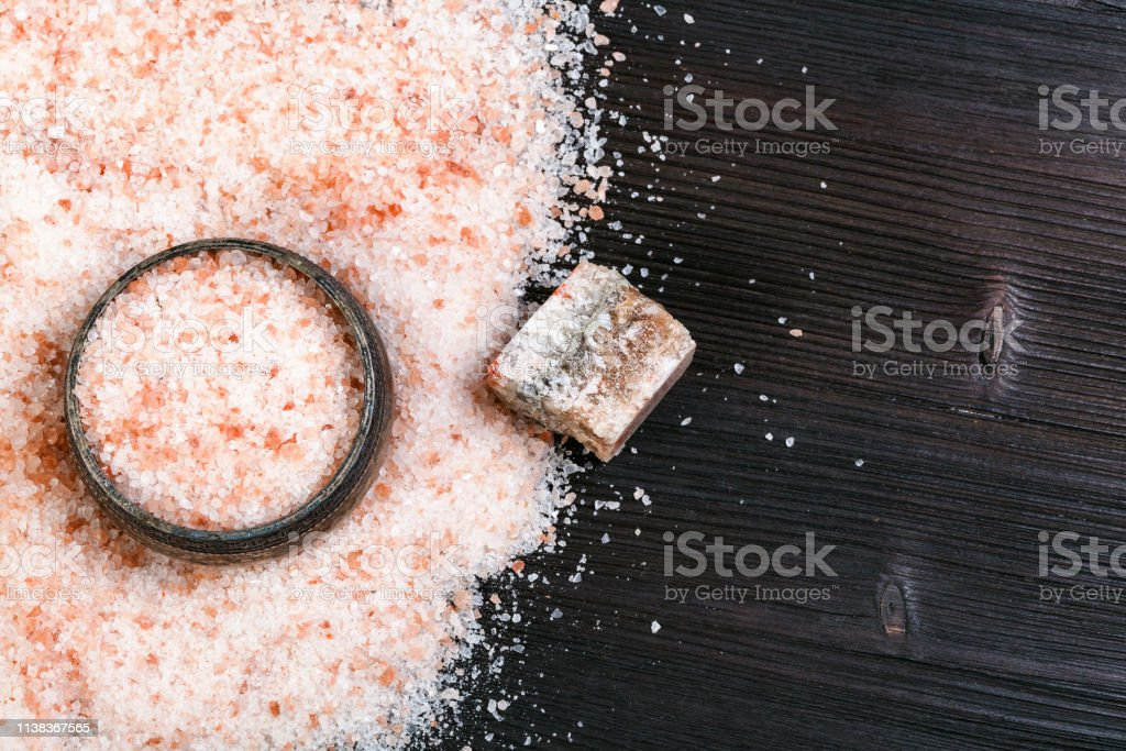 top view of salt cellar and pink Salt on table top view of silver salt cellar, rough natural pink Halite mineral and grained Himalayan Salt on dark brown wooden board Black Color Stock Photo