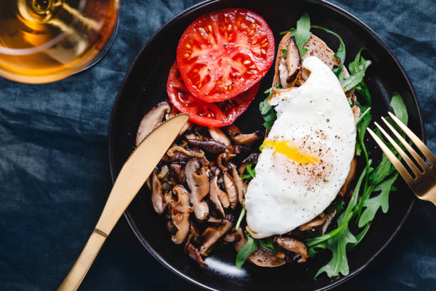 Top view of sandwich with fresh arugula, fried shiitake mushroom, shallot onion, egg served with tomatoes. stock photo