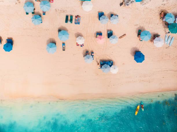 bovenaanzicht van het zandstrand met turquoise zeewater en kleurrijke blauwe paraplu's, luchtfoto drone schot - strandvakantie stockfoto's en -beelden