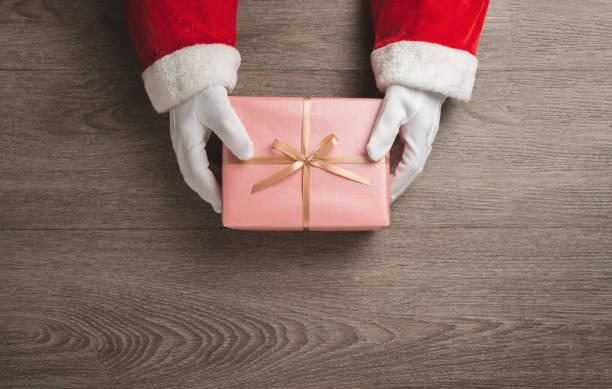 La vista superior de las manos de Santa Claus está sosteniendo una caja de regalo rosa con cinta de oro sobre fondo de madera. - foto de stock