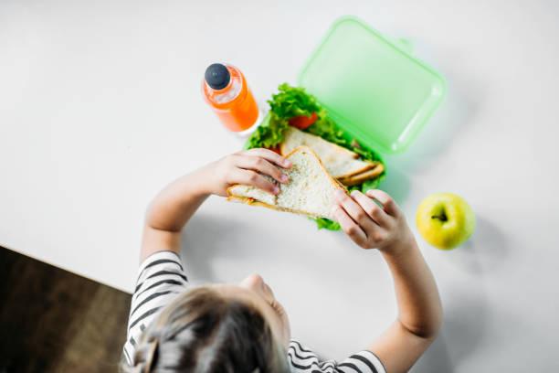 ovanifrån av skolflicka äter smörgås från matlåda - lunchlåda bildbanksfoton och bilder