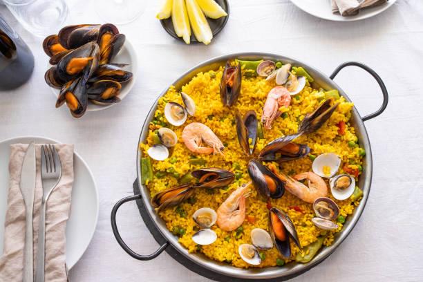 bovenaanzicht van zeevruchten paella met garnalen, kokkels, mosselen op saffraan rijst en groenten geserveerd in traditionele koekenpan op de tafel. - paella stockfoto's en -beelden