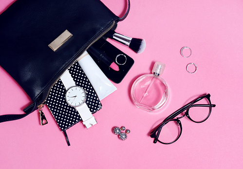 Top view of set female accessories on pink flat lay