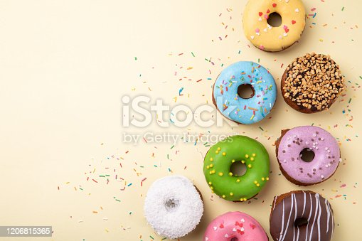istock Top view of set of donuts on yellow background. Flat lay, copy space. 1206815365
