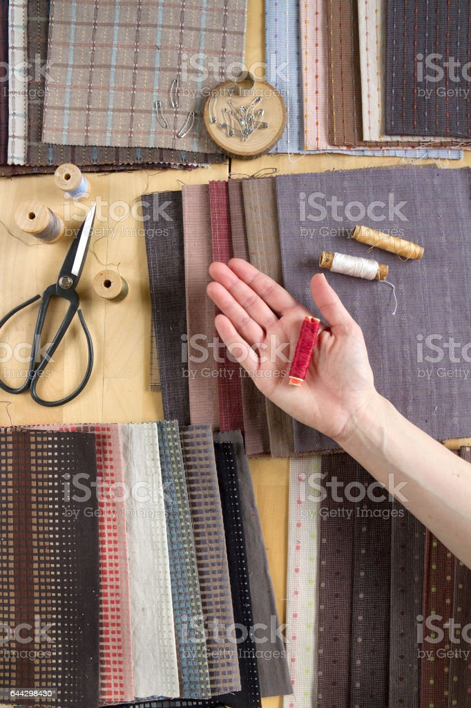 Top view of sewing table with fabrics, supplies for home decor or quilting project and woman's hand стоковое фото