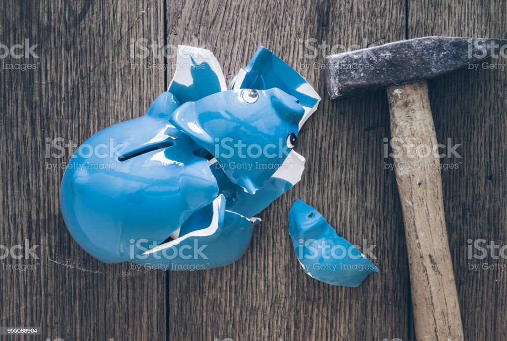 top view of shattered piggy bank and hammer on rustic wooden table stock photo