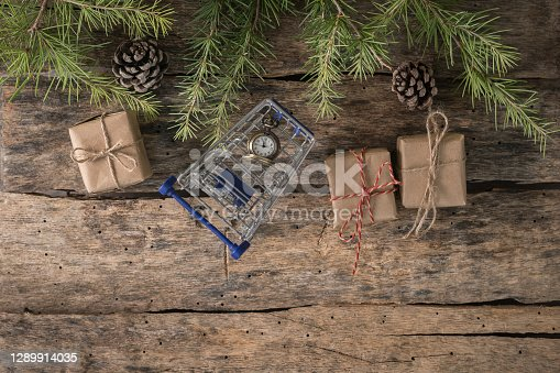 Top view of shopping cart and Christmas decorations with gift boxes.