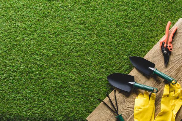 top view of shovels, hand rake, protective gloves and secateurs on wooden planks - sprzęt ogrodniczy zdjęcia i obrazy z banku zdjęć