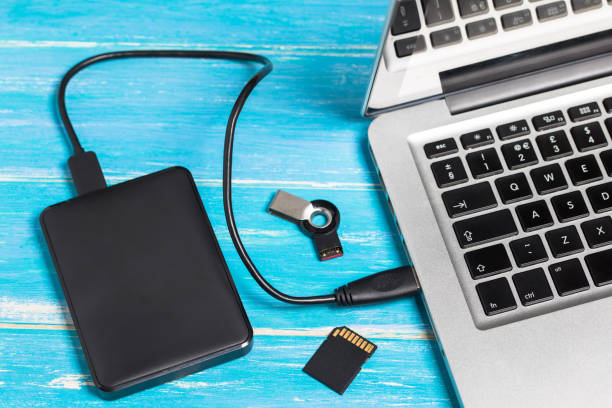 Top view of silver laptop / notebook with external hard drive disk HDD and SD card on wooden table with copy space Top view of silver laptop / notebook with external hard drive disk HDD and SD card on wooden table with copy space external hard disk drive stock pictures, royalty-free photos & images