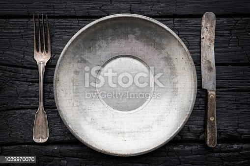 Empty plate with silverware on black background