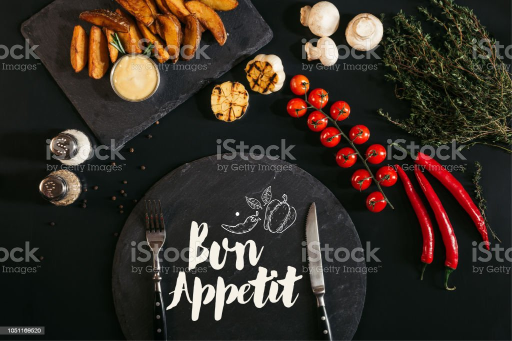 top view of slate board with 'bon appetit' lettering and fork and knife, baked potatoes, spices and vegetables on black stock photo