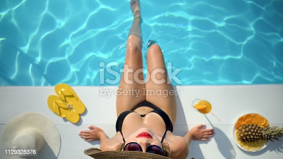 Top view of slim young woman in hat near swimming pool, enjoying vacation