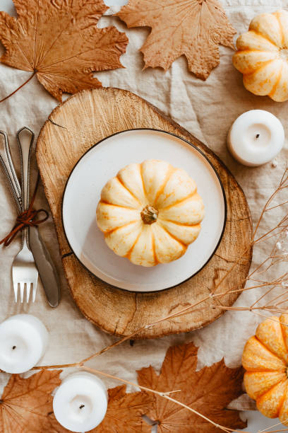Top view of small pumpkins on a wooden board decorated Autumn ornate. The concept of Thanksgiving and Fall time. stock photo