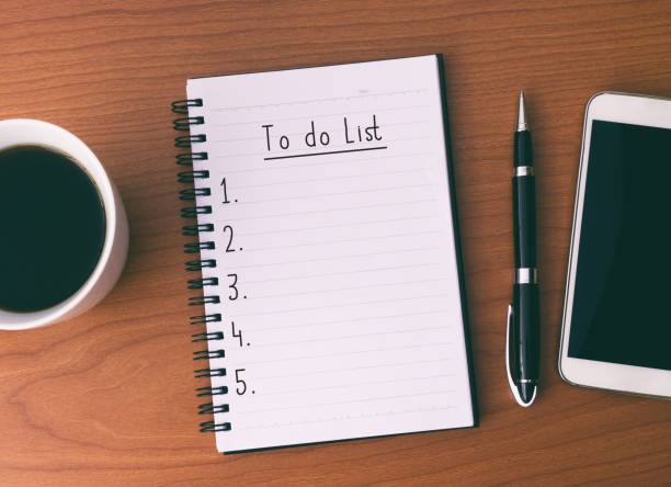 top view of smart phone, coffee, pen and notepad - to do list foto e immagini stock