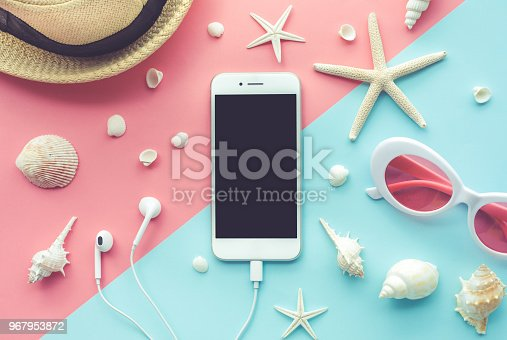 istock Top view of smartphone and element of vacation on color background. Summer, travel concept 967953872