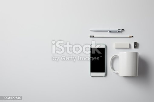top view of smartphone with various supplies and cup on white surface for mockup