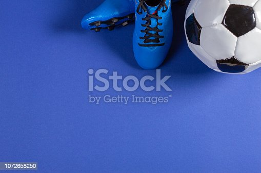 Top view of soccer ball and pair of soccer football sports shoes on blue color background