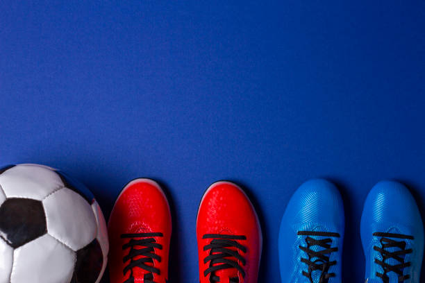 Top-Ansicht des Fußballs und zwei Paar Fußball-Sportschuhe auf blauem Hintergrund – Foto