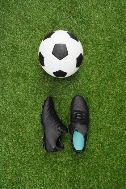 vue de dessus du ballon de soccer avec paire de chaussures de sport sur herbe - imitant un animal photos et images de collection