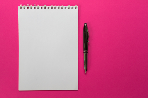 Design concept - Top view of spiral school notebook and pen collection on pink background for layout.