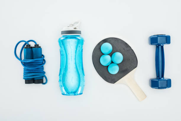 top view of sport bottle near ping pong balls and sport equipment isolated on white - racket sport stock pictures, royalty-free photos & images